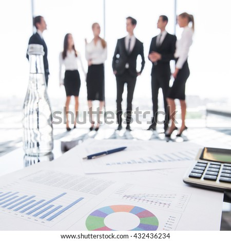 Close-up of financial reports and calculator, business people team standing in the background - stock photo