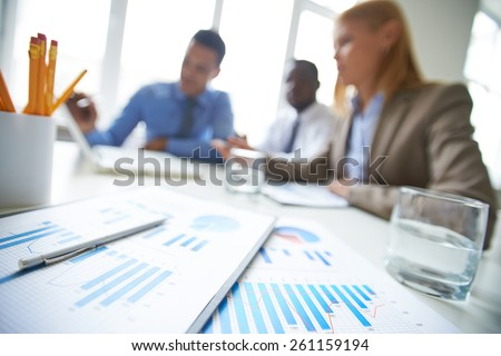 Close-up of financial reports with clipboards on table