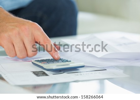 Close up of finger touching calculator in bright living room - stock photo