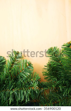 Close up of fir tree branch over wooden background with copyspace - stock photo