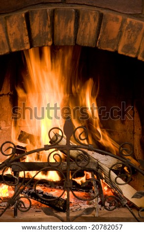 Close-up of fire in brown brick chimney set on in the evening - stock photo