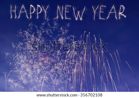 Close-up of fireworks in a night sky. In new year eve. Happy new year text. - stock photo