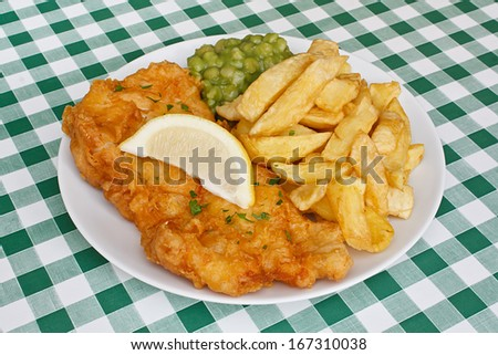 Close up of fish and fries garnished with mushy peas and a slice of lemon, on a traditional Diner table top. - stock photo