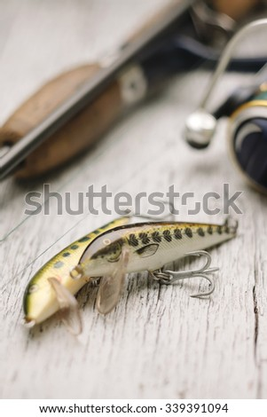 Close-up of fishing lures with rod on wooden background. - stock photo