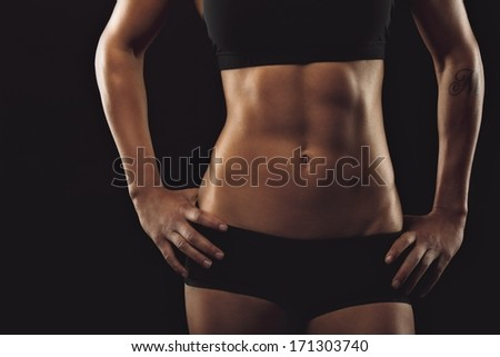 Close up of fit woman's torso with her hands on hips. Female with perfect abdomen muscles on black background - stock photo