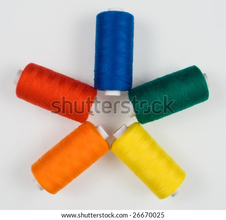 close up of five colored sewing spools - stock photo