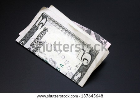close up of five dollar bills folded