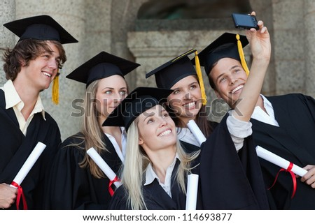 Close-up of five graduates taking a picture of themselves in front of the university