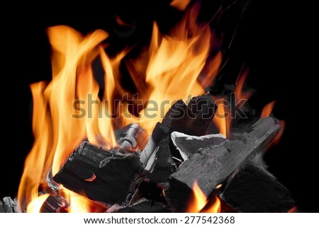 Close-up Of Flaming Charcoal In The Fireplace On The Black Background - stock photo