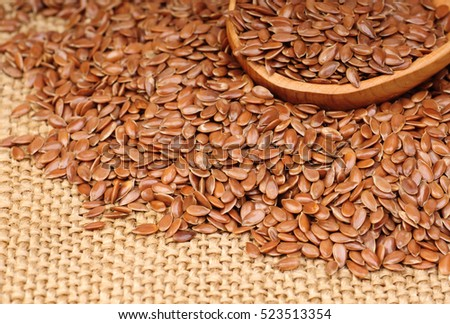 close up of flax seeds in wooden spoon on canvas background