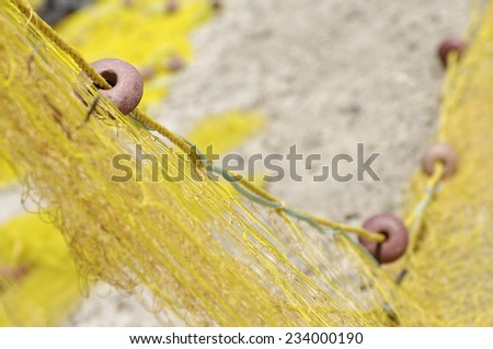 close up of float on yellow fishing nets on beach - stock photo