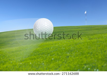Close-up of flying golf ball over beautiful golf course