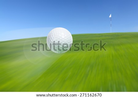 Close-up of flying golf ball over blurred course