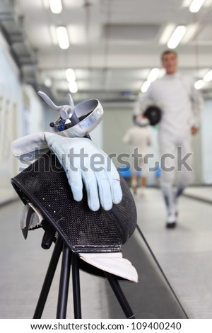 Close up of foil, mask and white glove at background ot going fencer. Shallow DOF. - stock photo