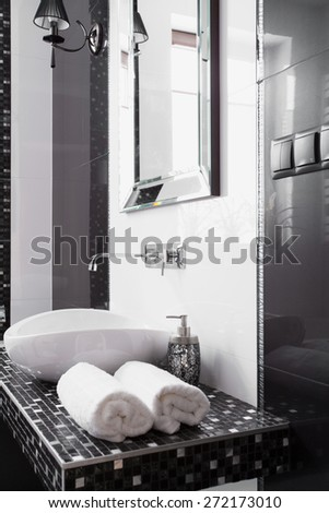 Close-up of folded towels near basin in modern bathroom - stock photo