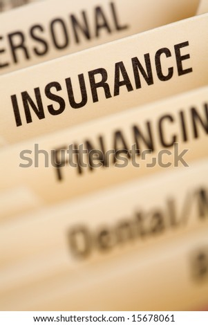 Close up of folder for household bills with focus on insurance section