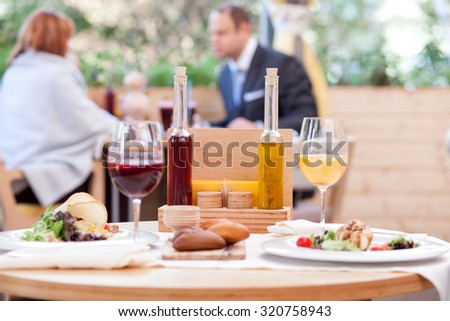 Close up of food and two glasses of aperol on the table in restaurant. The man and woman are sitting and talking with joy on background