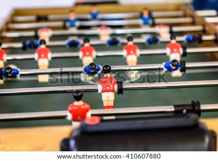 Close up of foosball Table Soccer Game match figures. Football Kicker Game with blue and red figurines.