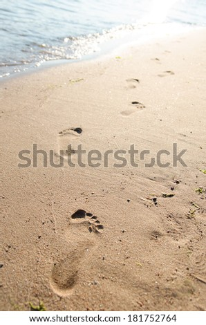 Close up of footprints on the beach sand at the sunset - stock photo