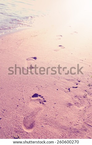 Close up of footprints on the beach sand at the sunset with instagram effect retro vintage filter - stock photo