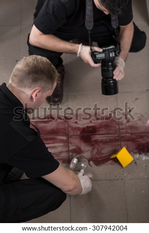Close-up of forensic technicians taking evidences of crime - stock photo
