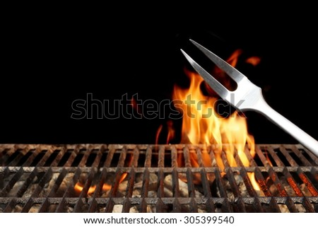 Close-up of Fork and Empty Flaming Charcoal BBQ Grill With Bright Flames On The Isolated Black Background. Weekend Barbecue Party  Or Picnic Concept. - stock photo