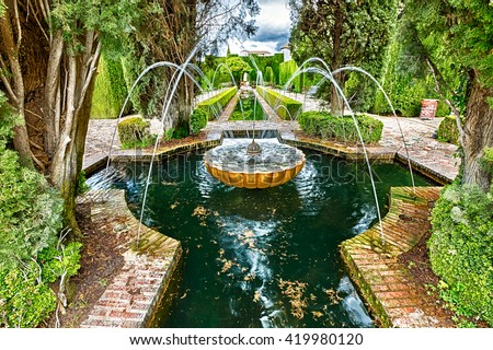 Close up of fountain in the famous avenue of cypress trees, Generalife gardens near Alhambra complex, Granada, Andalucia, Spain, one of the most beautiful in the world and is a Unesco heritage. - stock photo
