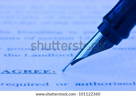 close-up of fountain pen and printed agreement - stock photo