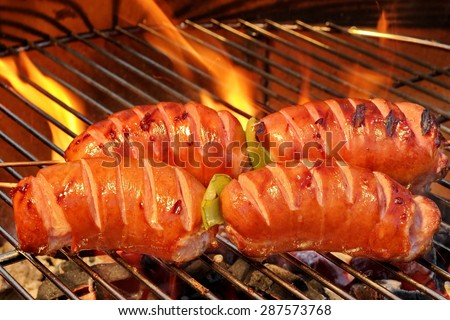 Close-up Of Four Fatty  Sausage On The Hot BBQ Charcoal Grill And Flames In The Background - stock photo