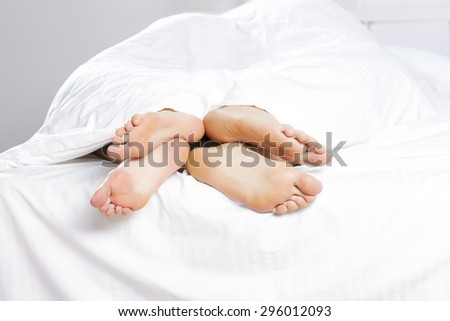 Close up of four feet in a bed
