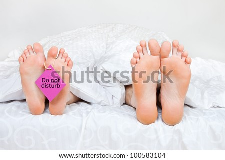 Close up of four funny feet in a bed - stock photo