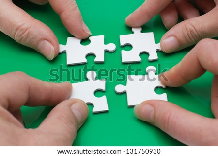 Close up of four people hands with puzzle - stock photo