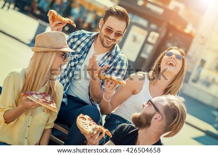 Close-up of four young cheerful people eating pizza,they are enjoying together. - stock photo
