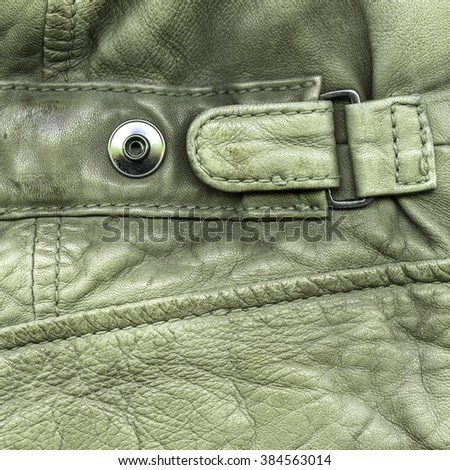close-up of fragment of green leather jacket,strap, button - stock photo