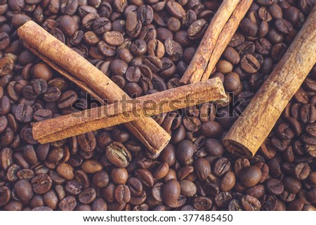Close-up of fragrant cinnamon sticks on coffee beans as background. Selective focus. - stock photo