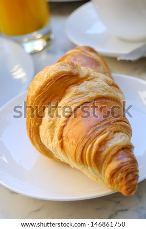 close-up of french breakfast with croissant in white plate and orange juice in background