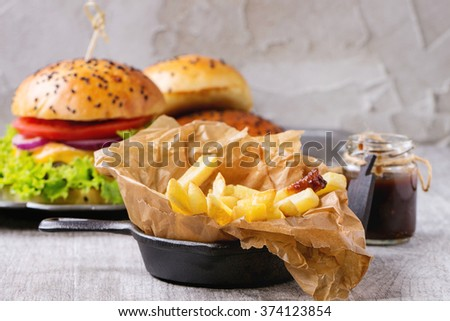 Close up of french fries potatoes in backing paper with Fresh homemade burger at background, served with jar of ketchup sauce over gray wooden table. Rustic style. - stock photo