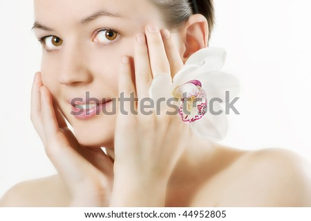 Close-up of fresh and beautiful woman face with flower