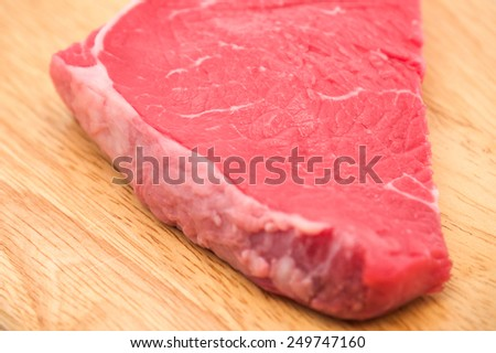 Close up of fresh and raw red beef meat on wooden cutting board for food background  - stock photo