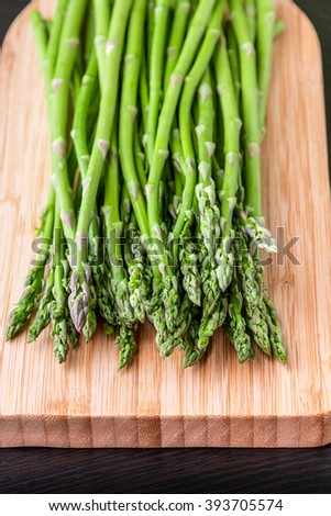 Close up of fresh asparagus on wooden board. Selective focus on tips of asparagus. - stock photo