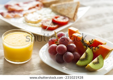 Close up of fresh fruit and orange juice with continental breakfast plate in background. - stock photo