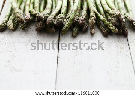 Close up of fresh green asparagus on wooden table - stock photo
