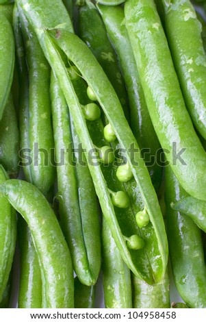 Close-up of fresh green pea pods with water drops.