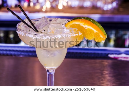 Close up of fresh lime margarita with ice cubes in margarita glass sitting on bar top garnished with orange and lime wedges - stock photo