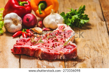 Close-up of fresh meat steak with spices on wooden background - stock photo