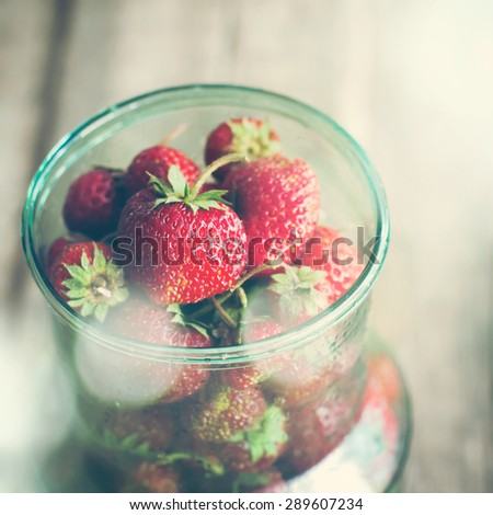 Close up of Fresh Organic Strawberry in Jar on Wooden Table with Boke Effect - stock photo