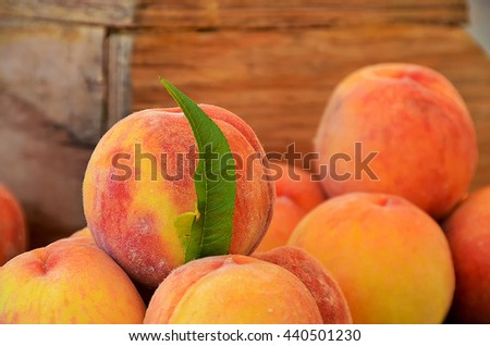 close up of fresh peaches with single peach leaf at the farmer's market - stock photo