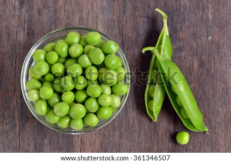 Close up of fresh peas on wooden table