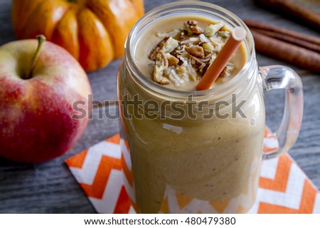 Close up of fresh pumpkin coconut apple smoothie in mason jars garnished with toasted coconut and pecans sitting on orange chevron napkin surrounded by ingredients