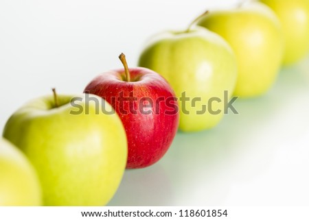 """Close up of fresh red apple standing out from row of green apples, concept """"Dare to be different."""". - stock photo"""